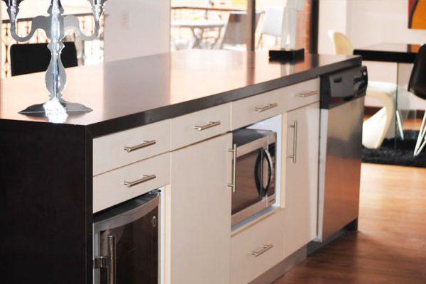 Vista general de la cocina, frente en vidrio laminado para gabinetes y acabado en chapilla de madera natural pintada con poro cerrado.